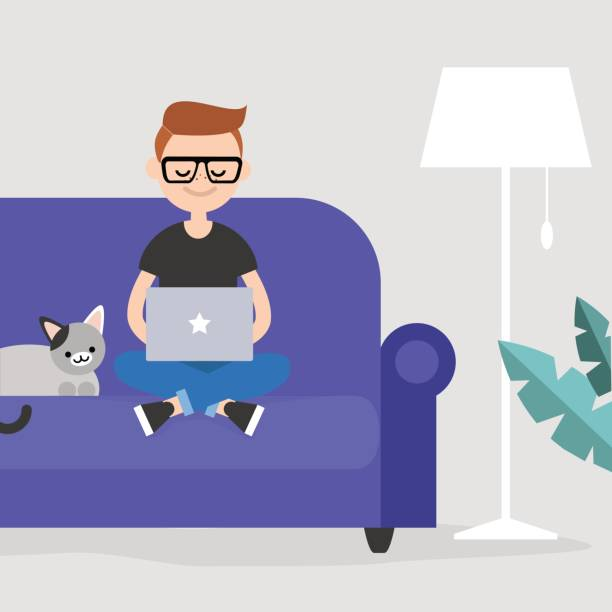 Student sitting on couch next to pet cat, with laptop in lap.
